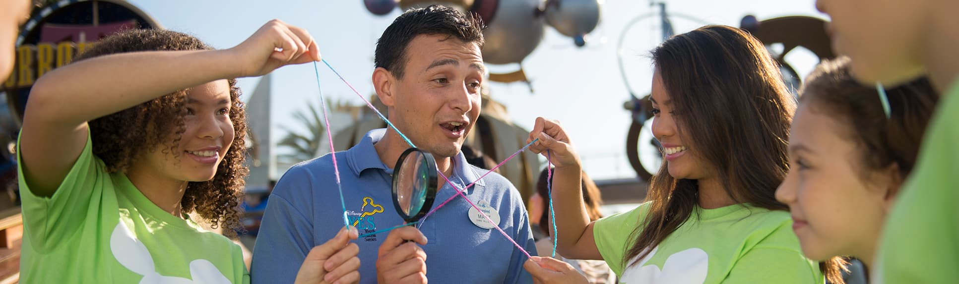 A Cast Member holding a magnifying glass and high school children holding a string in the shape of 2 triangles
