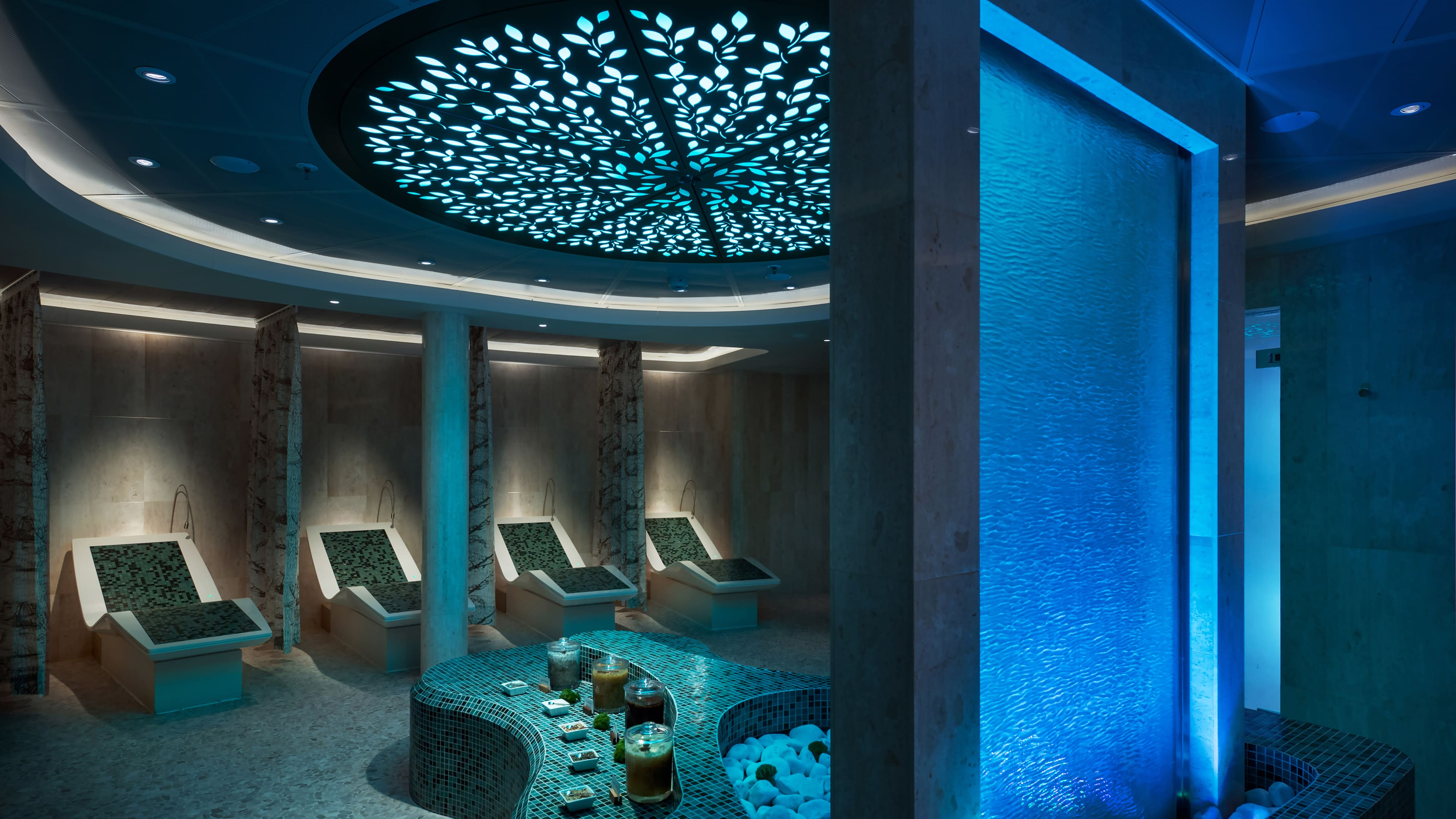 A spa with a fountain, seats and candles