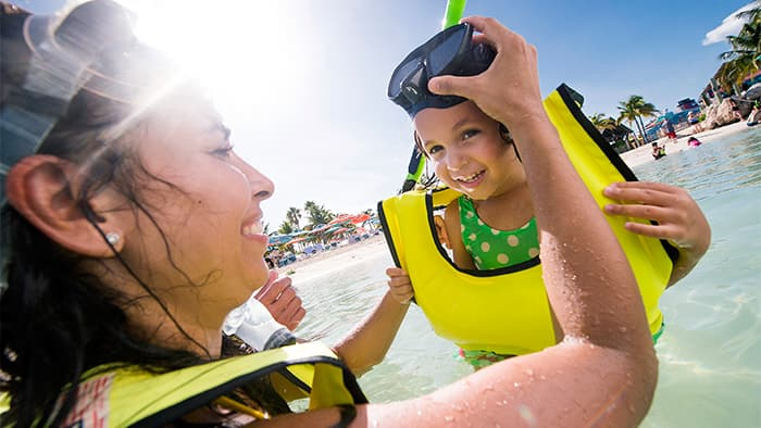 Uma mãe sorri, enquanto ajuda a filha a colocar a máscara de mergulho, no mar, em uma praia da Castaway Cay.