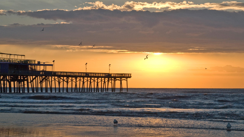 La silueta de un muelle y aves marinas contra el brillante atardecer de Galveston, Texas