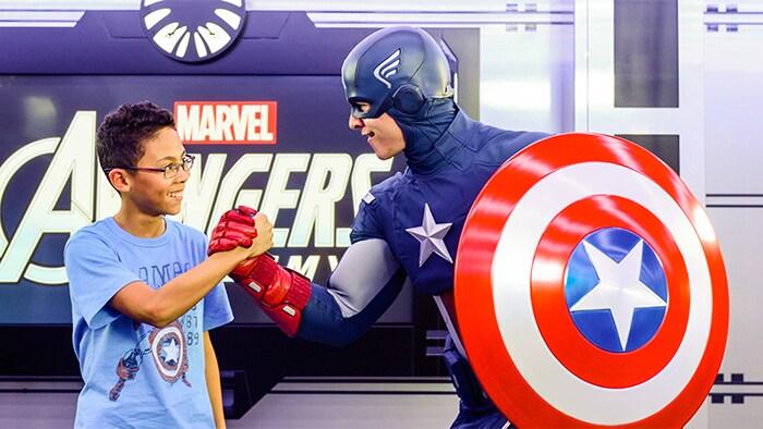 Captain America saluda de mano a los niños frente al letrero de Marvel Avengers