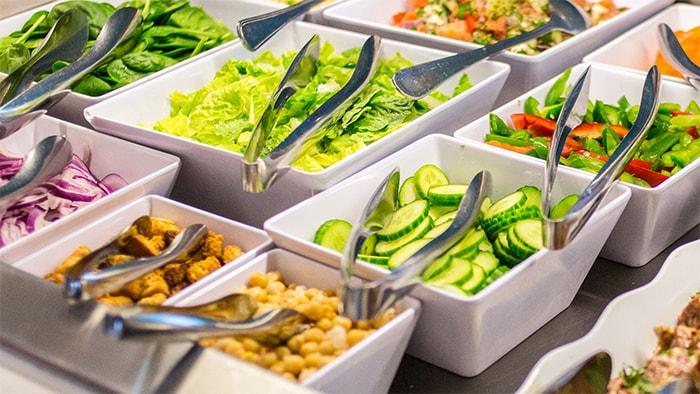 Barra de ensaladas que incluye lechuga, espinaca, pimientos, pepinos, y mezclas de vegetales preparados