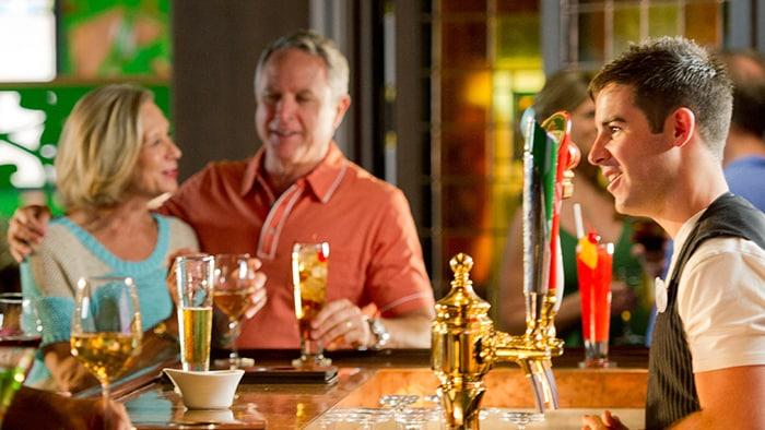 Un hombre y una mujer disfrutan una bebida alcohólica en el bar, mientras el barman los atiende