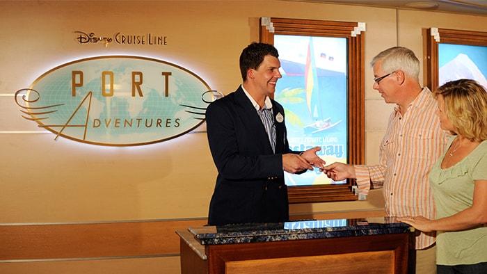 Dos visitantes de Disney Cruise Line hablan con un miembro del elenco en el mostrador de Aventuras en el Puerto del barco
