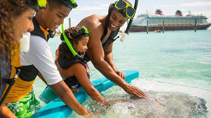 Una familia deja de bucear con snórkel para acariciar delfines con el crucero de Disney en el fondo
