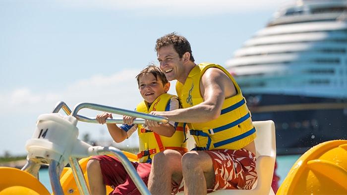Un papá y su hijo van juntos en un triciclo de agua mientras en el fondo se ve un barco crucero