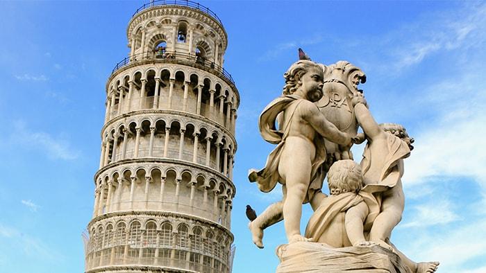 La Torre de Pisa y una estatua de ángeles junto a ella