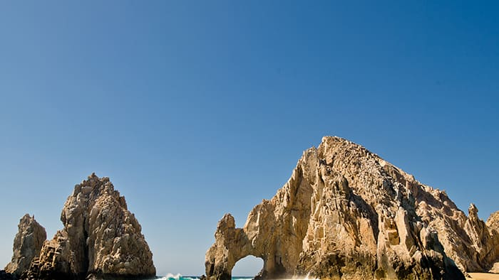 Una estructura natural de roca dentada en el mar, con un orificio tan grande que cabría un bote pequeño
