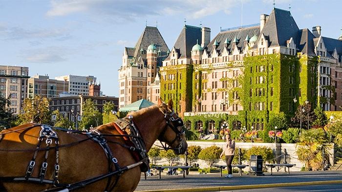 Un carruaje con caballo al otro lado de la calle de un edificio victoriano con hiedra en algunas paredes