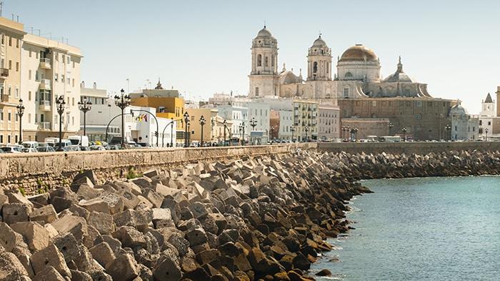 Blocos de concreto protegem a costa ao lado de prédios antigos em Cádiz, na Espanha