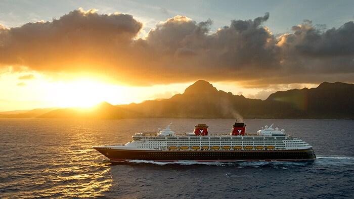 O Disney Wonder, um navio com vários andares de altura, no mar em frente a uma costa acidentada, ao entardecer.