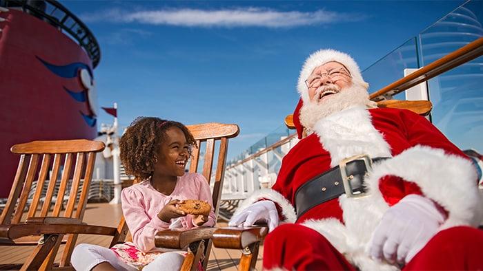 Una niñita ofrece una galleta a Santa Claus mientras descansan en sillas de madera en una cubierta de un crucero de Disney