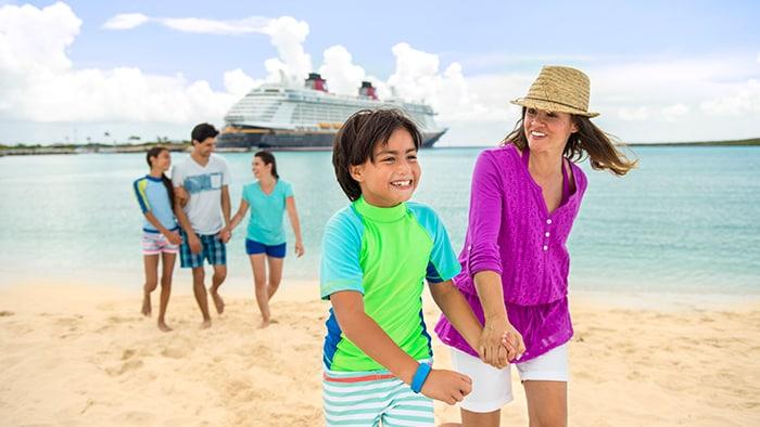 Uma família de cinco pessoas passeia em uma praia com um navio da Disney Cruise Line atracado ao fundo.
