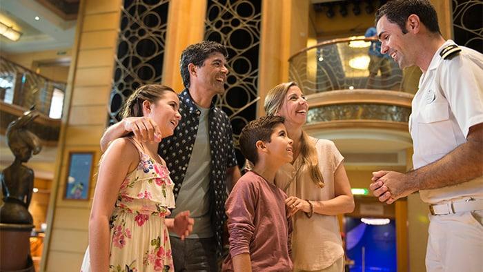 Um membro da tripulação interage com uma família de quatro pessoas em meio a decoração art nouveau no lobby de um navio.