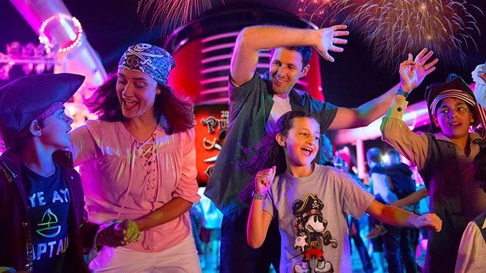 Une famille dans des costumes de pirates danse sur le pont d'un navire de croisière