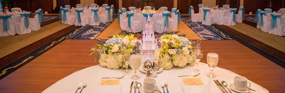 A table arrangement of a castle and bouquet for the bride and groom in a ballroom