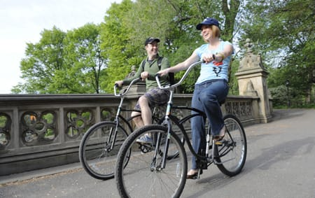 A man and a woman ride bikes along a path in the city