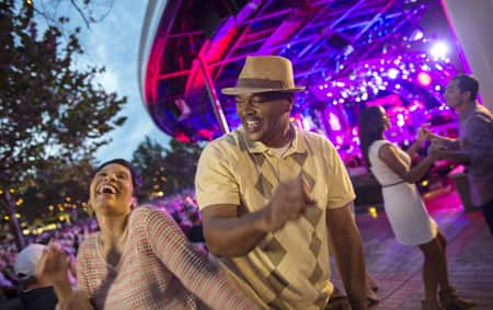 A woman and a man show off their dance moves at an outdoor music venue