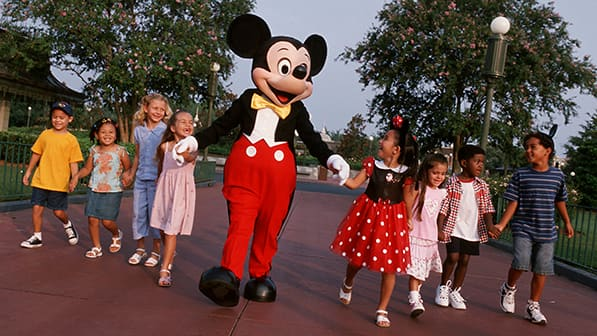 Children holding hands with one another and Mickey Mouse