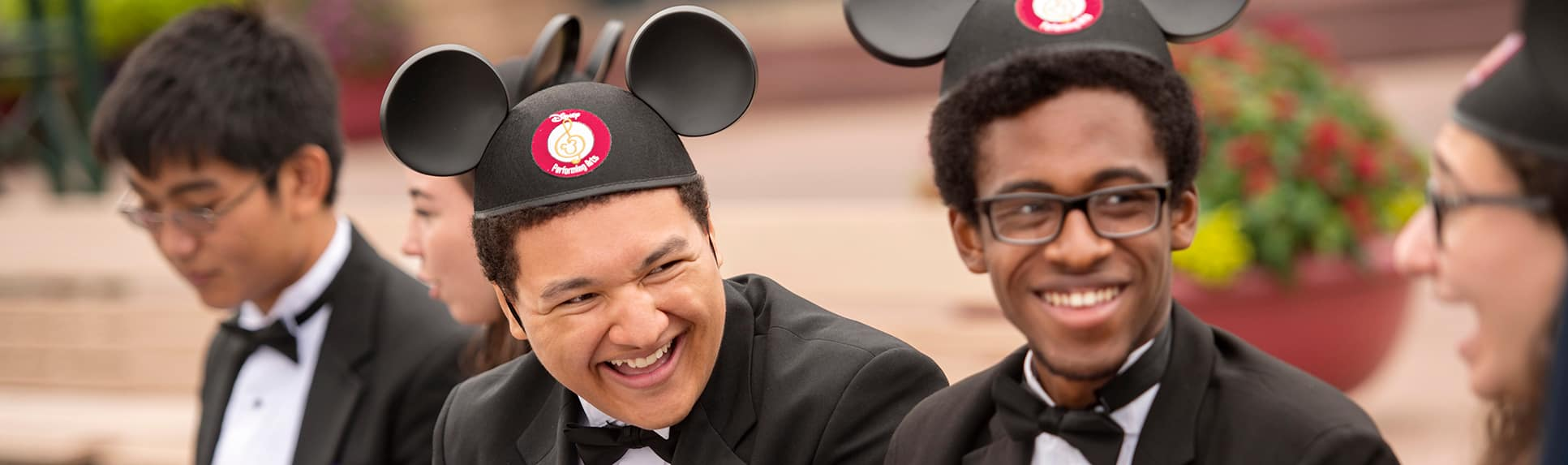 Young adults wearing formal clothing and Mickey ears