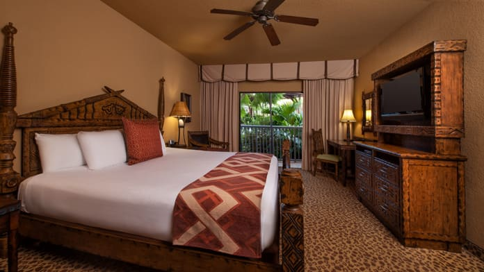 A bedroom with a bed  TV and desk  with sliding glass doors leading to. Rooms   Points   Disney s Animal Kingdom Villas   Kidani Village