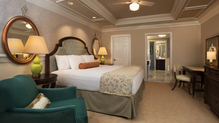 A Bedroom With Bed Quilted Headboard Armchair Mirrors And Dresser