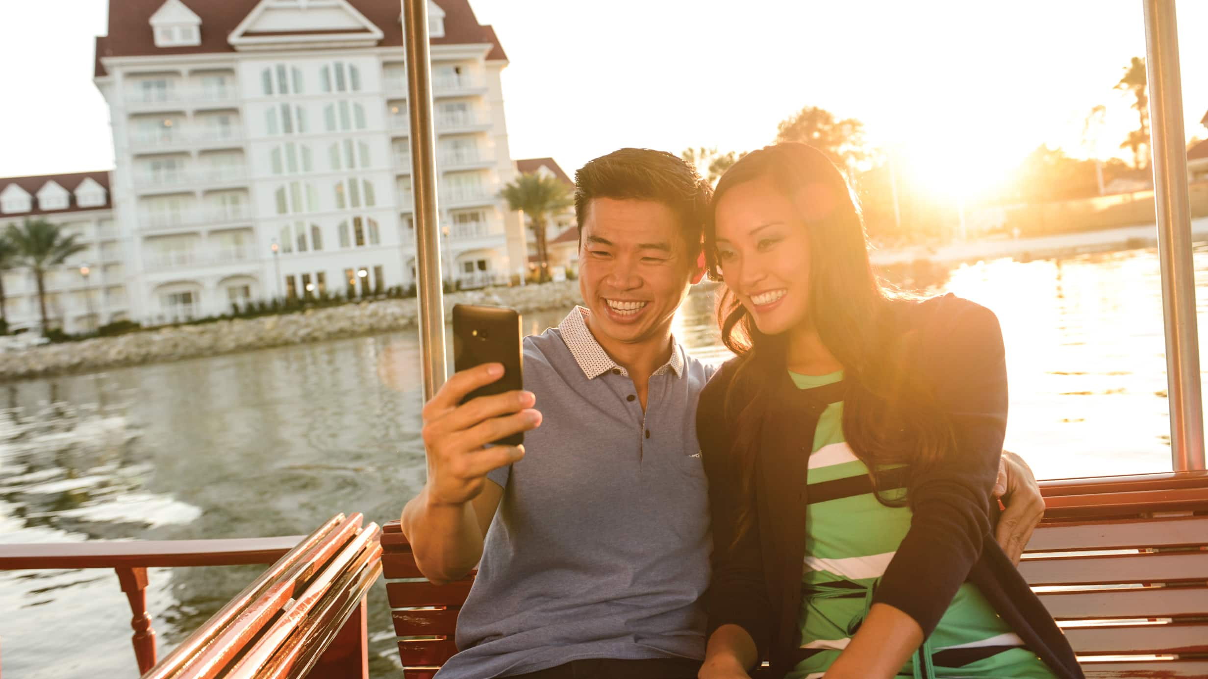 A man and woman take a selfie while riding on a boat