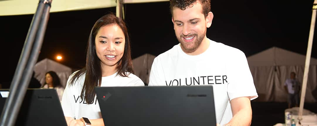 Sitting side by side, 2 volunteers work on laptop computers inside one of the race tents