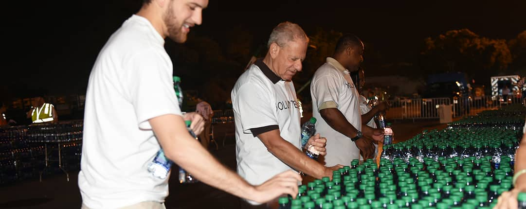 Before sunrise, volunteers grab several water bottles from a sea of tables filled with bottles for passing runners